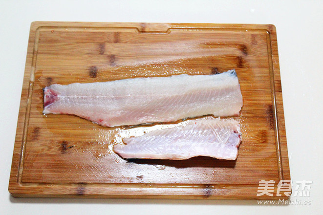 片下来的鱼骨切块备用 一手轻按鱼肉,一手拿切片刀,将刀身倾斜30度-45